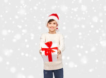 Smiling happy boy in santa hat with gift box. Winter holidays, presents, christmas, childhood and people concept - smiling happy boy in santa hat with gift box Stock Image