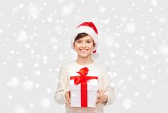 Smiling happy boy in santa hat with gift box. Winter holidays, presents, christmas, childhood and people concept - smiling happy boy in santa hat with gift box Royalty Free Stock Photo