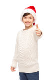 Smiling happy boy in santa hat showing thumbs up Stock Image