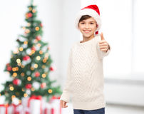Smiling happy boy in santa hat showing thumbs up Royalty Free Stock Image