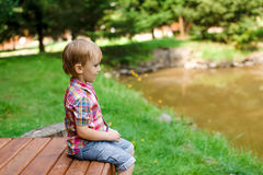 Smiling happy boy sitting on bench near lake. Summer time weeken Stock Photo