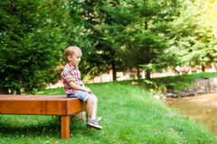 Smiling happy boy sitting on bench near lake. Summer time weeken Royalty Free Stock Photos