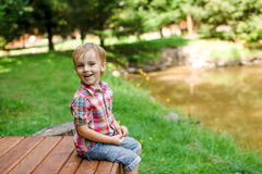 Smiling happy boy sitting on bench near lake. Summer time weeken Royalty Free Stock Photography