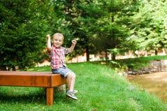 Smiling happy boy sitting on bench near lake. Summer time weeken. Smiling happy boy sitting on the bench near lake. Summer time weekend mood Royalty Free Stock Image