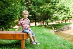 Smiling happy boy sitting on bench near lake. Summer time weeken. Smiling happy boy sitting on the bench near lake. Summer time weekend mood Royalty Free Stock Photo