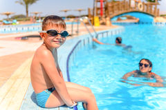 Smiling happy boy sitting at the edge of a pool Royalty Free Stock Photos