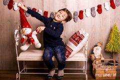 Smiling happy boy waiting christmas and Santa. Sitting on a bed Stock Images