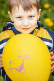Smiling happy boy whith yellow balloon. On green background Stock Image