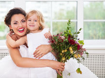 Smiling happy bride and a flower girl indoors Royalty Free Stock Photo