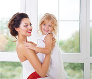 Smiling happy bride and a flower girl indoors Stock Photos