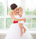 Smiling happy bride and a flower girl indoors Stock Photo