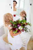 Smiling happy bride and a flower girl indoors Royalty Free Stock Image