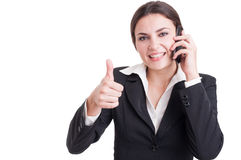 Smiling happy business woman showing like or thumb-up gesture. While having a phone conversation Royalty Free Stock Image
