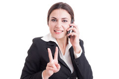 Smiling happy business woman showing victory or peace gesture. While having a phone conversation Stock Photo