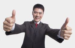 Smiling happy businessman giving thumbs-up with both hands to the camera, studio shot Royalty Free Stock Photography
