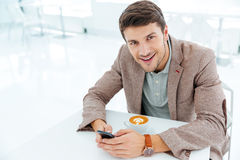 Smiling happy businessman holding smart phone and looking at camera Royalty Free Stock Photo