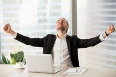 Smiling happy businessman celebrating finished work project  at. Smiling happy businessman raising arms up celebrating finished work project at workplace Stock Photography