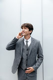 Smiling happy businessman in suit having a mobile phone conversation. Isolated against white Royalty Free Stock Images