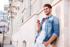 Smiling happy casual man using mobile phone outdoors Royalty Free Stock Image