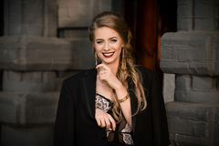 Smiling happy cheerful fashionable girl in black dress, jacket on wall stone background. Happiness concept. Picture of pretty styl royalty free stock photo