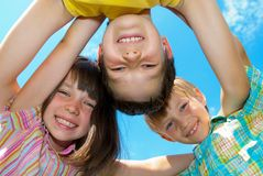 Smiling happy children. In a circle with blue sky background stock photography