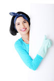 Smiling cleaning woman showing blank sign board. Stock Photos