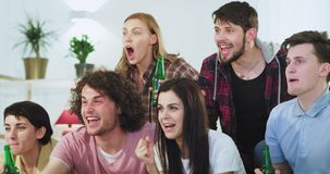 Smiling and happy concentrated group of friends watching a football match they excited yelling and cheers with beer. Bottles while their team win the match stock video