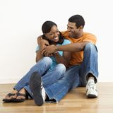 Smiling happy couple. Happy, smiling African American couple sitting on floor snuggling royalty free stock photo