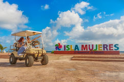 Couple driving a golf cart at tropical beach on Isla Mujeres, Mexico. Smiling and happy couple driving a golf cart at tropical beach on Isla Mujeres, Mexico Stock Photography