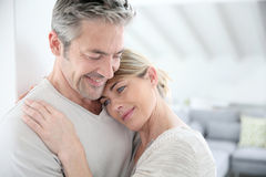 Smiling happy couple embracing indoors Stock Images