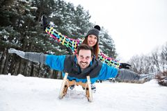 Smiling happy couple enjoy in sledding at snow winter day royalty free stock photo