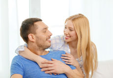 Smiling happy couple at home. Love, family and happiness concept - smiling happy couple at home Royalty Free Stock Images