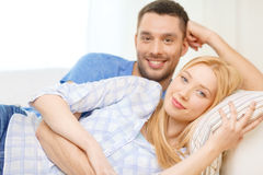 Smiling happy couple at home. Love, family and happiness concept - smiling happy couple at home Royalty Free Stock Photo