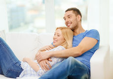 Smiling happy couple at home. Love, family and happiness concept - smiling happy couple at home Royalty Free Stock Image