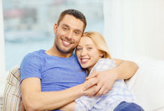 Smiling happy couple at home. Love, family and happiness concept - smiling happy couple at home Stock Photography
