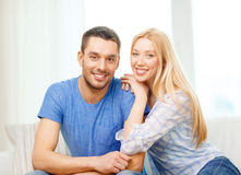 Smiling happy couple at home. Love, family and happiness concept - smiling happy couple at home Stock Photos