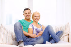 Smiling happy couple at home. Love, family and happiness concept - smiling happy couple at home Stock Image
