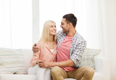 Smiling happy couple at home. Love, family and happiness concept - smiling happy couple at home Stock Images