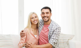 Smiling happy couple at home. Love, family and happiness concept - smiling happy couple at home Royalty Free Stock Photography