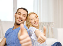 Smiling happy couple at home showing thumbs up. Love, family and happiness concept - smiling happy couple at home showing thumbs up Stock Image
