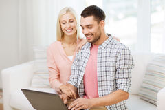 Smiling happy couple with laptop computer at home Royalty Free Stock Photo