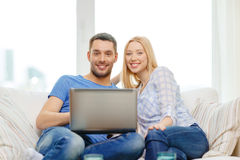 Smiling happy couple with laptop at home Royalty Free Stock Images