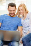 Smiling happy couple with laptop at home Royalty Free Stock Image