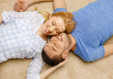 Smiling happy couple lying on floor at home Royalty Free Stock Photos