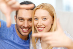 Smiling happy couple making frame gesture at home. Love, family and happiness concept - smiling happy couple making frame gesture at home royalty free stock image