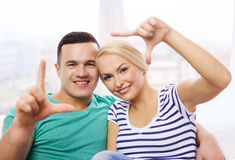 Smiling happy couple making frame gesture at home Stock Image