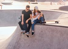Smiling happy couple of students are sitting at skatepark with their longboards royalty free stock photos