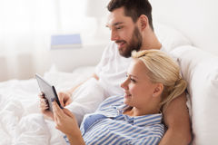 Smiling happy couple with tablet pc in bed at home Royalty Free Stock Images