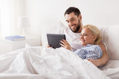 Smiling happy couple with tablet pc in bed at home Stock Images