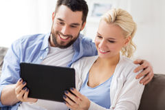 Smiling happy couple with tablet pc at home Stock Photo